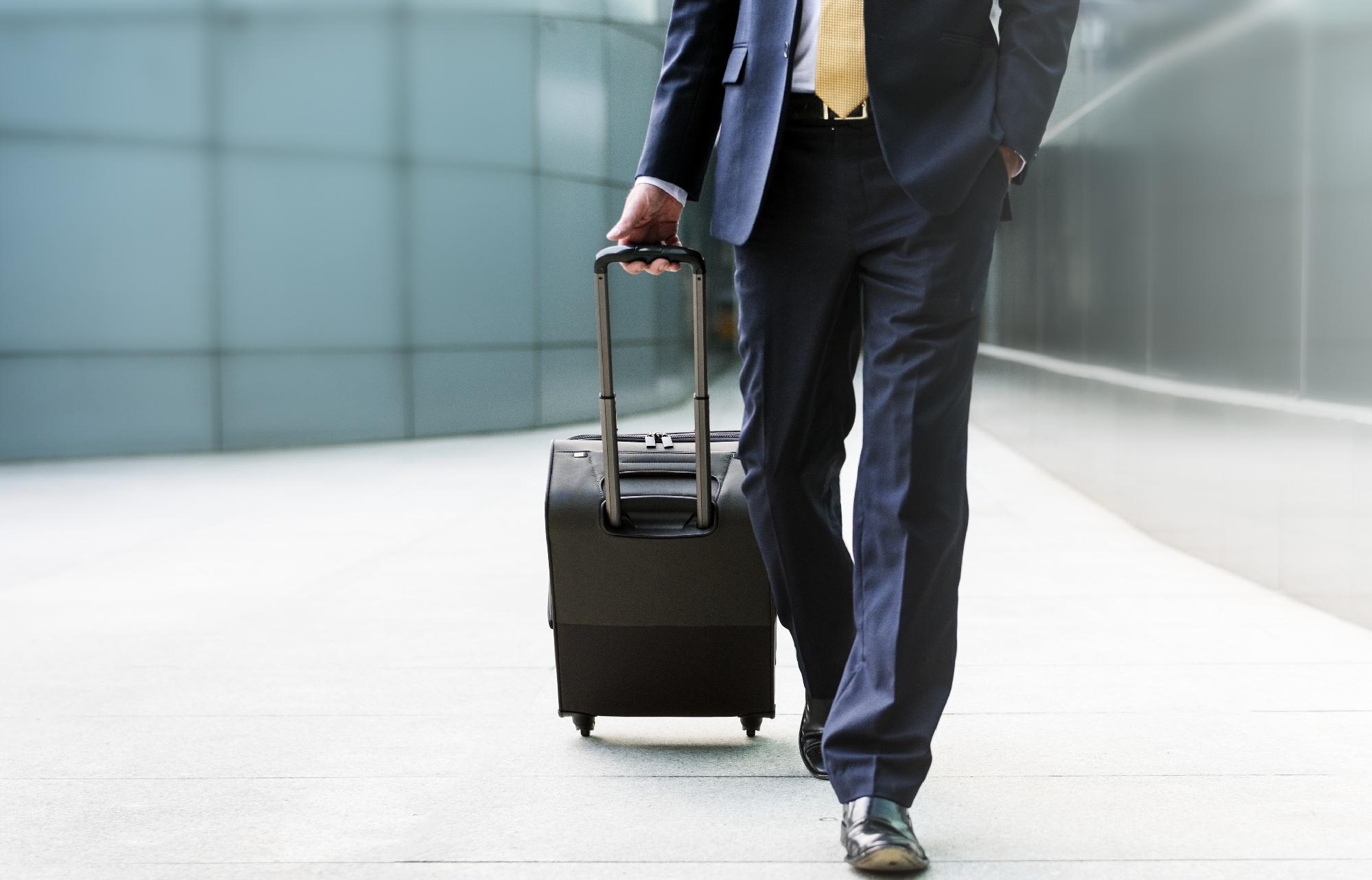 Man in a suit walking with a suitcase